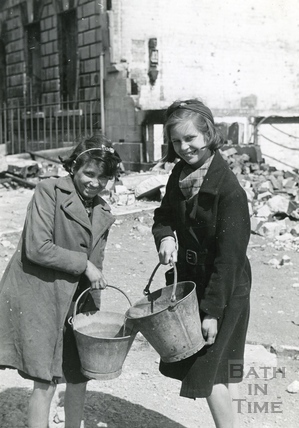 Two young girls happily go to fill their buckets outside 19 Green Park Buildings, 4th May 1942