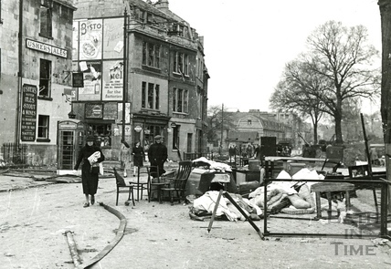 Walking past a pile of salvaged furniture on the Upper Bristol Road, Bath, April 1942