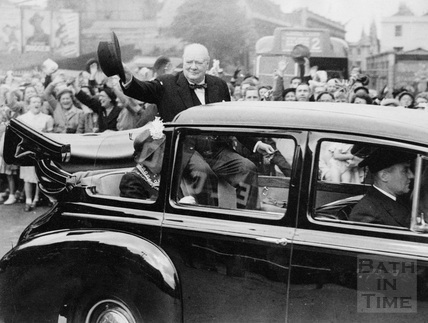 Winston Churchill in an open topped car being cheered by the public lining the route1950