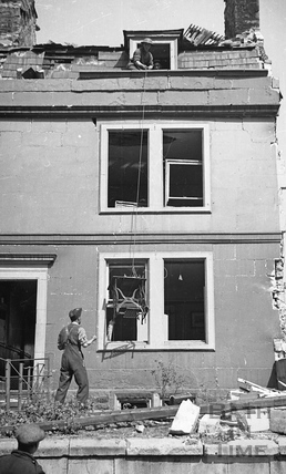 A sewing machine being lowered down from a bombed building, April 1942