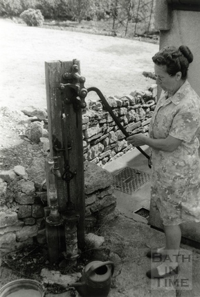 Mrs Phyllis Quintin of School House, Withyditch using her old water pump to help beat the drought in August 1976