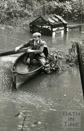Mr G Mealing in the canoe he used to rescue birds from a flooded fowl house, Oct 1960