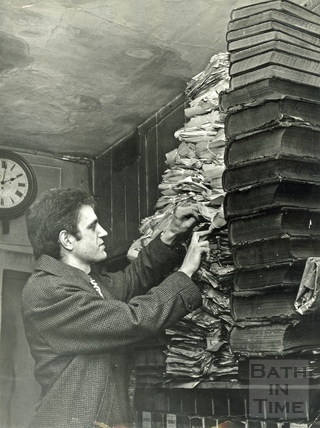 Russell Frears inspects a pile of ledgers and papers at Bowlers, Corn Street, 24 April 1972