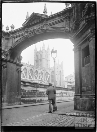 View under arch on York Street to Abbey with gentleman in foreground