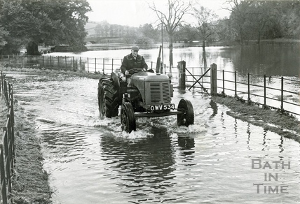 A farmer drives his tractor through the floods c.1960