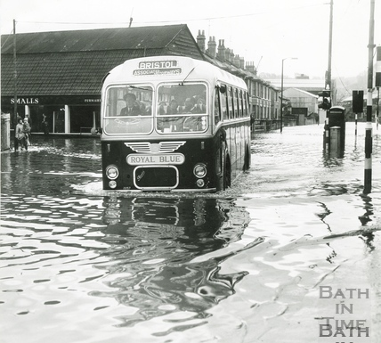 A Bristol Associated Motorways Royal Blue coach splashes through the floods c.1968