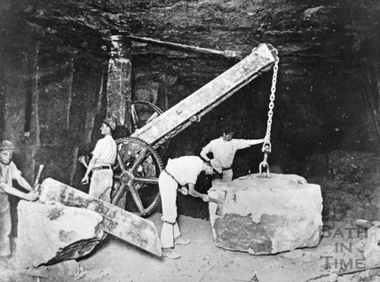 Quarrymen with crane lifting stone block