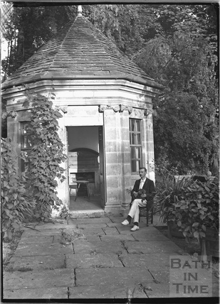 A gentleman sitting outside garden gazebo, Iford Manor c.1920s