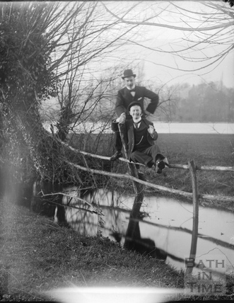 Two smartly dressed men beside an unidentified stream on a flooded plain c.1900s