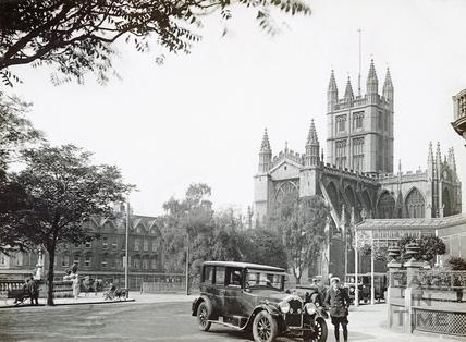 A chauffeur waits beside his car outside the Empire Hotel, Orange Grove c.1932