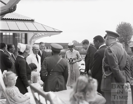 Emperor Haile Selassie poses for the camera as a nurse takes his picture, Bath, October 1954