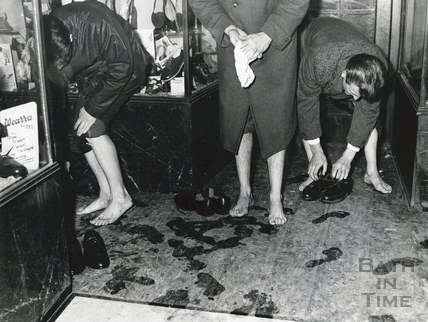 Taking off their shoes in a Bath shop doorway in the flood of 1960