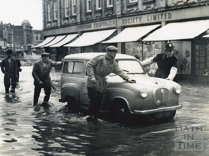 Pushing a waterlogged car in a flooded Chippenham High Street, 1960