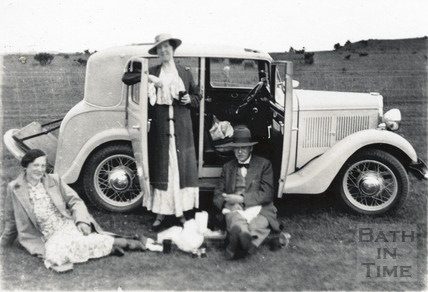 The photographer, his wife Violet and female friend picnic with the car, possibly on Bathampton Down c.1920s