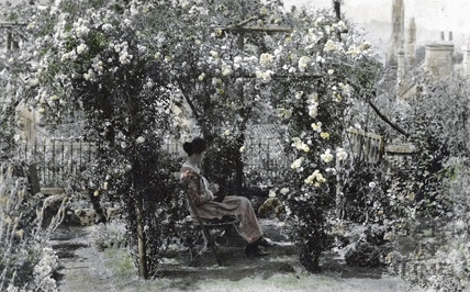 A slightly hand tinted photograph of the photographer's wife Violet at the bottom of their garden at 32 Sydney Buildings c.1930