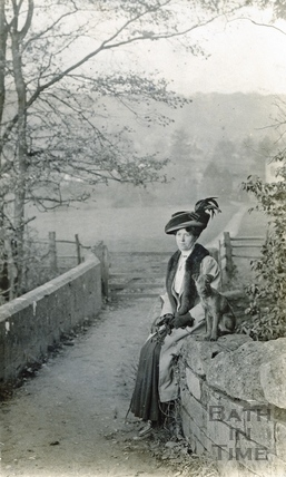 Violet, the photographer's wife and pet dog posing on a stone bridge, possibly over the Kennet and Avon Canal c.1910