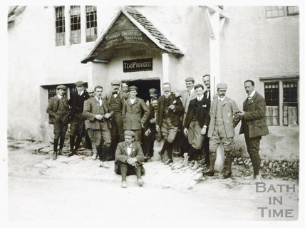 The photographer and a group of men pose outside a tea room at Castle Combe c.1892
