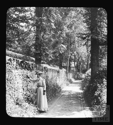 Titled 'A Shady Lane' a woman poses beside a wall on an unidentified lane, c.1892
