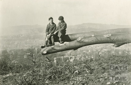 The photographer's twin boys balancing on a fallen tree trunk c.1924