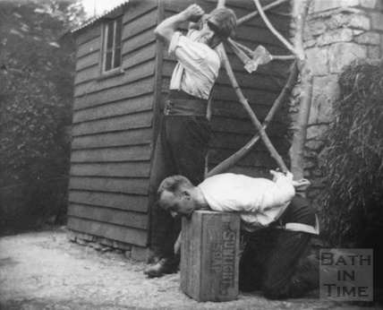 Herbert Noad pretends to behead Walter Noad in the garden behind Noad's Bakery, Bloomfield Road, Odd Down c.1950s