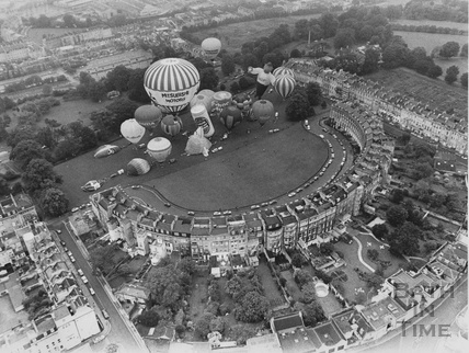 Aerial view of the rear of the Royal Crescent with a mass balloon launch on the Crescent Lawn in front. Date unknown
