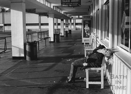 A girl slumped on a bench at the old bus station