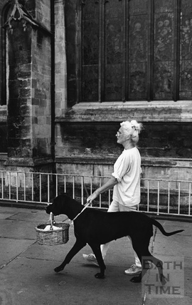A woman walking her dog with a basket in its mouth outside Bath Abbey