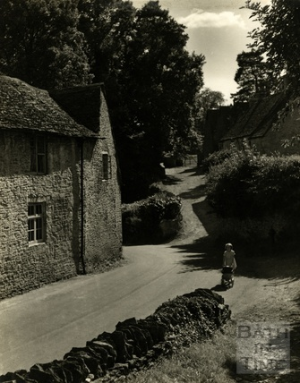A small girl and toy pram in Castle Combe, c.1960s?