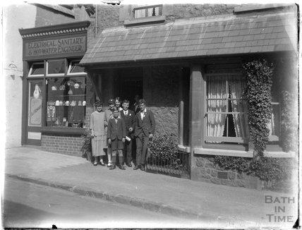 Group posing outside an electrical, sanitary and water engineering shop, Minehead 1926