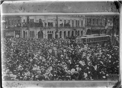 Crowded city scene with tram possibly Wellington, HMS New Zealand, c.1915