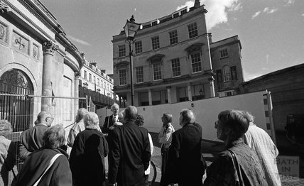A tour guide showing visitors around the Bath Street site of Thermae Bath Spa 2000.