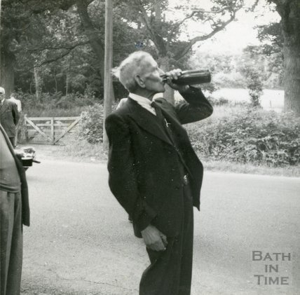 A merry Larkhall Inn regular swigs from a bottle during a trip, 1950s
