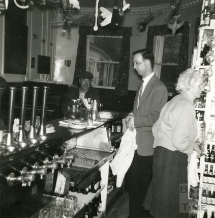 Interior of the Larkhall Inn with Ellen Harper behind the bar, 1940s