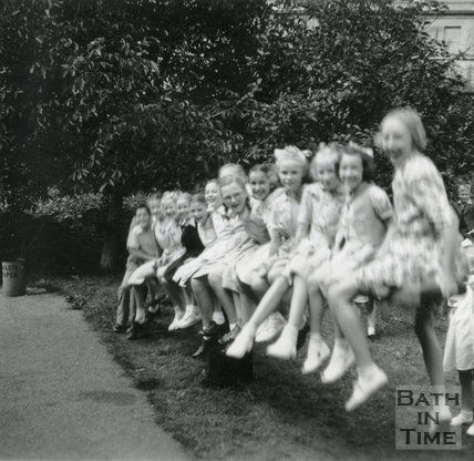 Children playing on the see-saw in the garden of the Larkhall Inn, July 1952