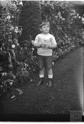 Portrait of a small boy in a garden, c.1915