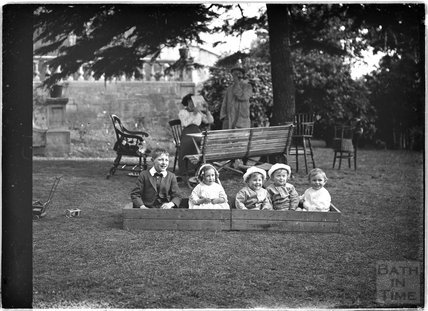 Children and their nanny in a garden paying c.1910