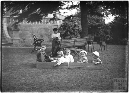 Children and their nanny in a garden paying c.1915