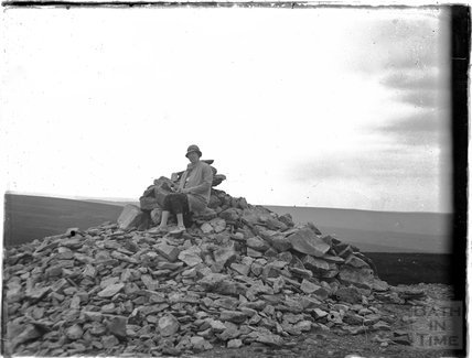 The photographer's wife Violet sitting on top of a pile of rocks, possibly Dartmoor c.1920s