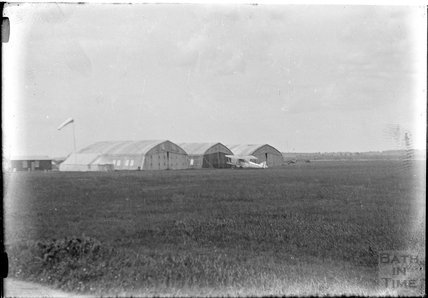 Unidentified aircraft hangers and a biplane c.1930s