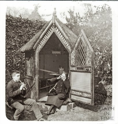 Boy and a girl outside a rustic garden hut, c.1890s