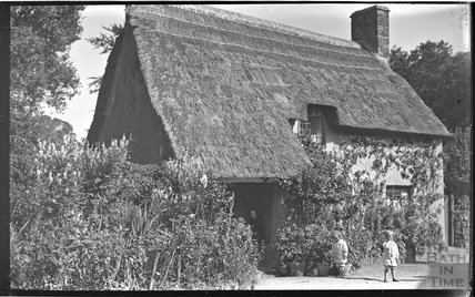 The photographer's twins outside a thatched cottage near Minehead 1914