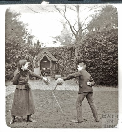 A girl and a boy fencing in the garden c.1890