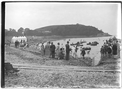 A group of spectators watching a seaside boating scene, Clevedon Beach, c.1920s