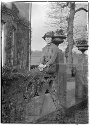 A young woman posing at the front of Monkton House, c.1900s