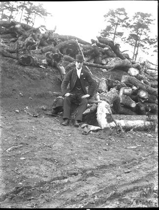 Unknown gent posing in front of a pile of logs, c.1900s