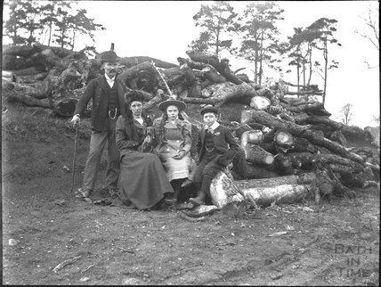 Unknown family portrait in front of a pile of logs, c.1900s
