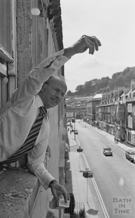 Toy master Eric Snook sprinkling rose petals out of the window, St James Street West, Bath  August 1977