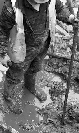 A workman stands in the watery basement of the Thermae Bath Spa development in his wellies, 4 April 2001