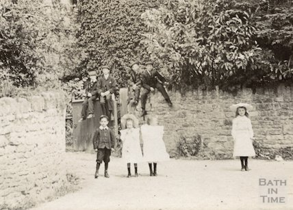 A charming group of children pose in the foreground of Nunney Castle c.1900
