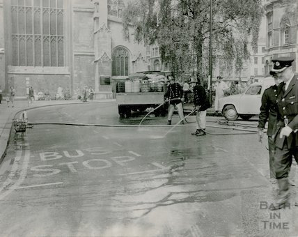 Firemen hose down the road in Orange Grove following a chemical spill, c.1960s